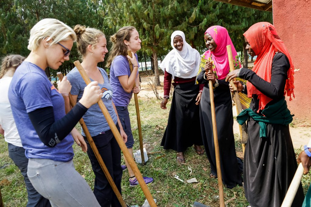 high school students taking a break from service with local community members in Tanzania